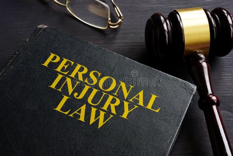人身受伤法律书籍和一张黑书桌 免版税库存照片