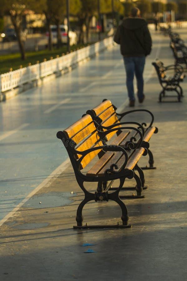 人轻易地胜过两三条木ironcast街道长凳在早晨太阳下 库存图片