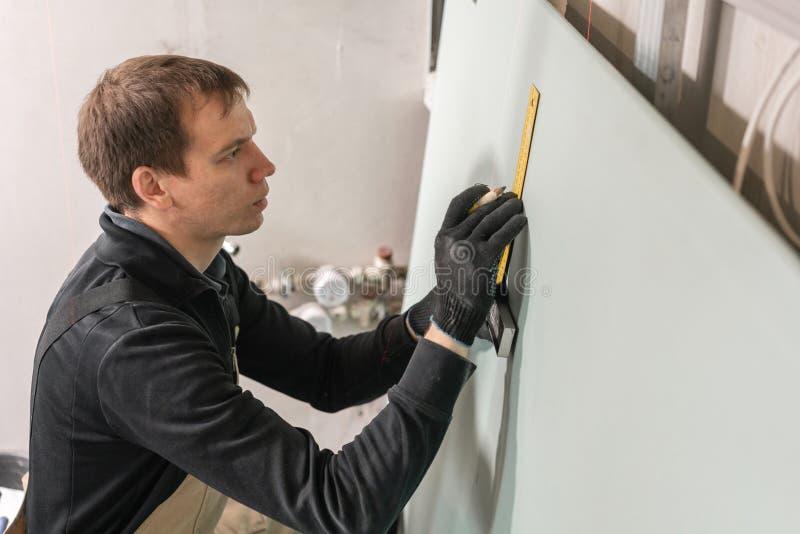 人运作的建造者在电子接线的干式墙做一个标号 金属干式墙建筑在一个房子里在期间 免版税库存照片