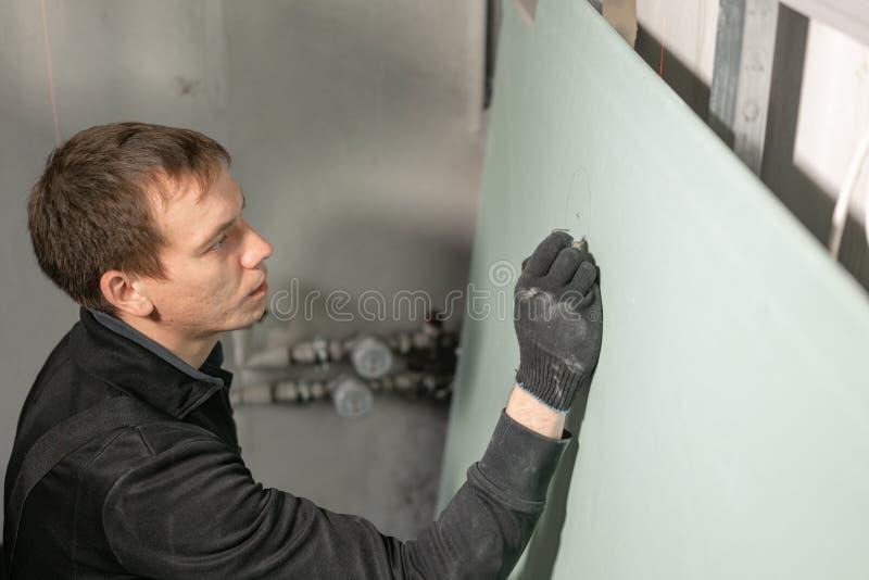 人运作的建造者在电子接线的干式墙做一个标号 金属干式墙建筑在一个房子里在期间 免版税库存图片