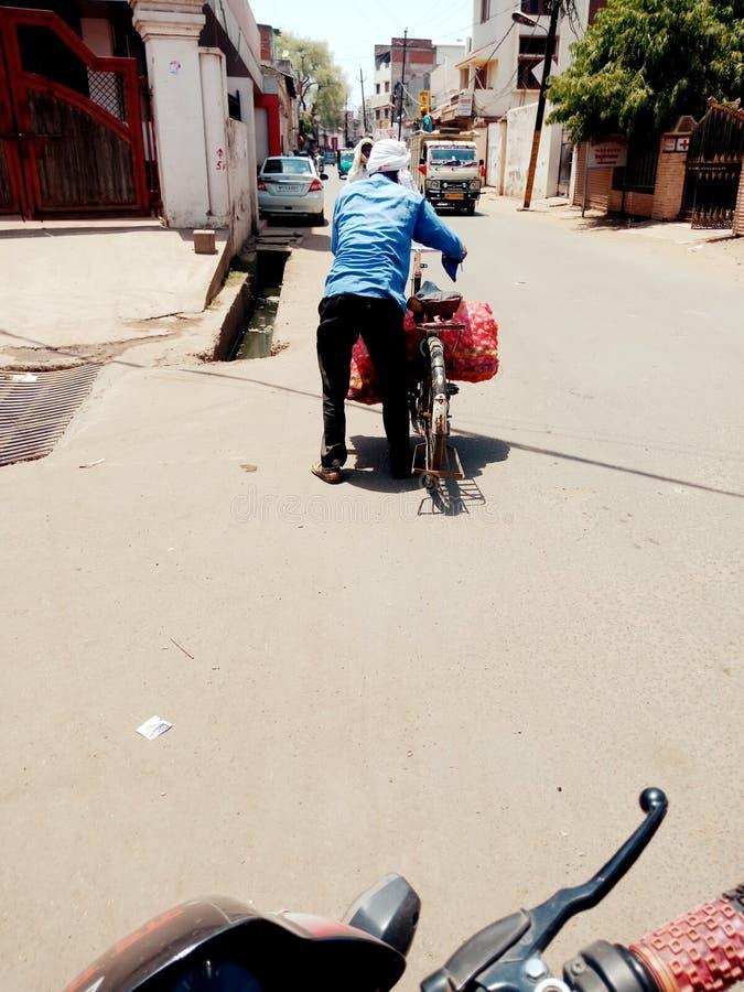 人运载了在自行车储蓄照片的重量 免版税图库摄影