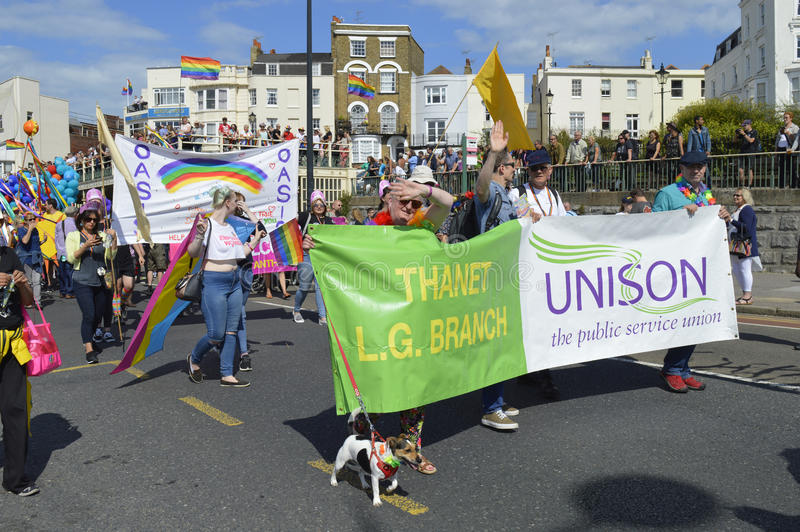 人进位标志和横幅在五颜六色的马盖特同性恋自豪日游行 库存图片