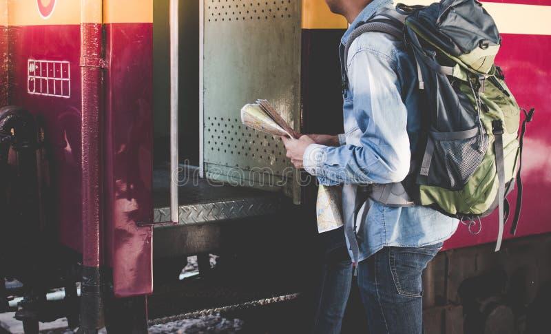 年轻人进入一列国际火车单独与在一个平台的旅行地图在火车站 免版税库存图片