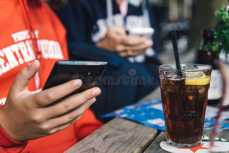 年轻人连接用电话和喝焦炭 免版税库存图片