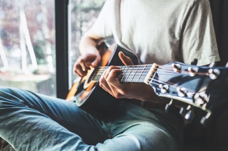 人递使用在吉他-接近的图象 免版税库存图片