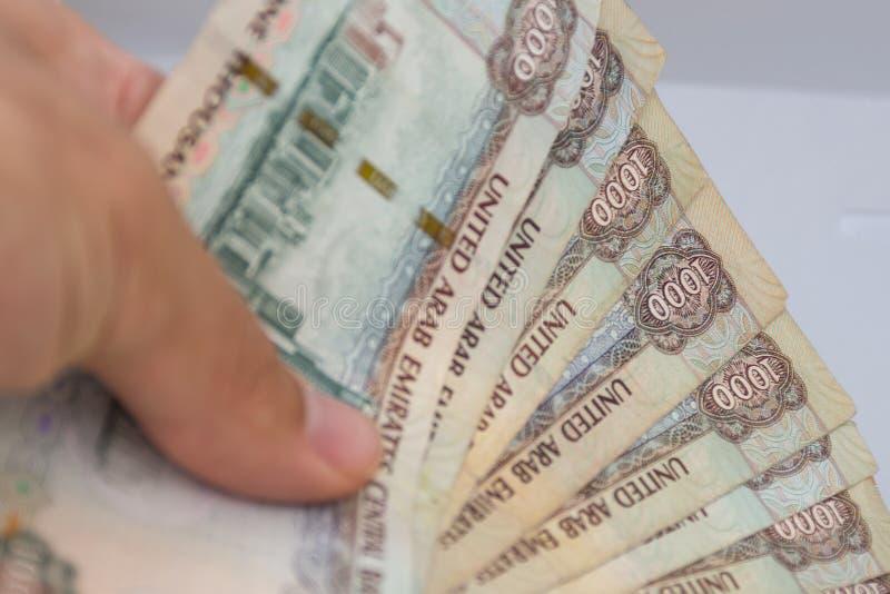 人递给阿拉伯联合酋长国阿拉伯联合酋长国的货币-一千迪拉姆笔记在白色背景延长 ?? 免版税库存图片