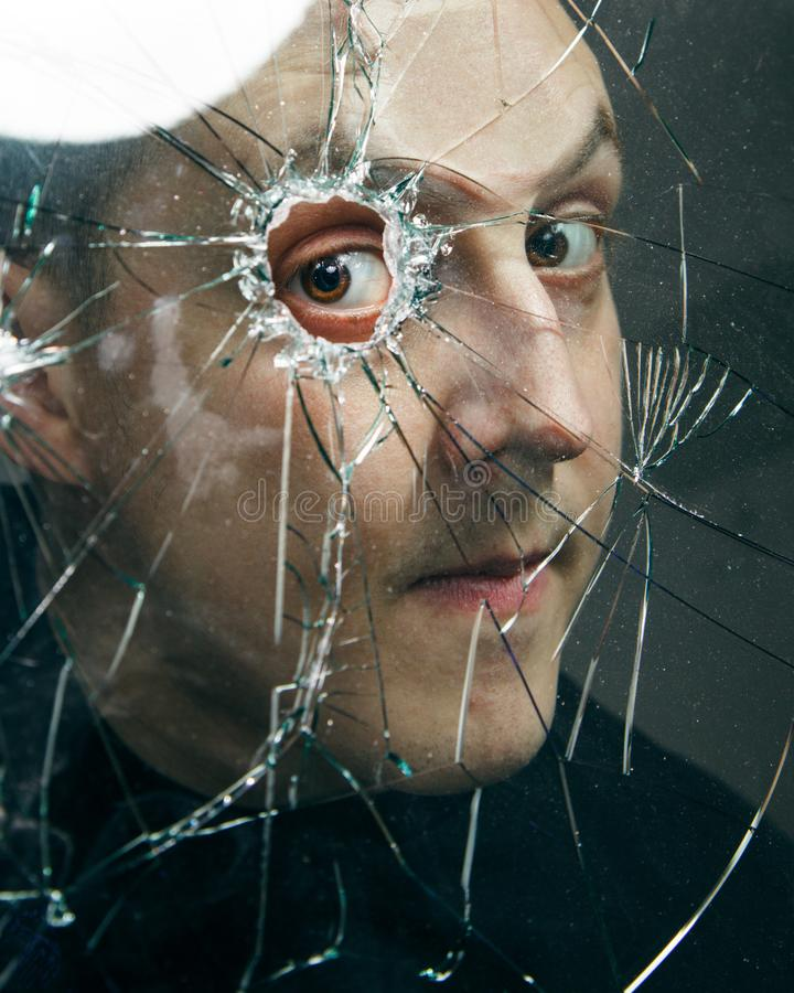 人通过残破的玻璃看 接近的纵向 免版税库存照片