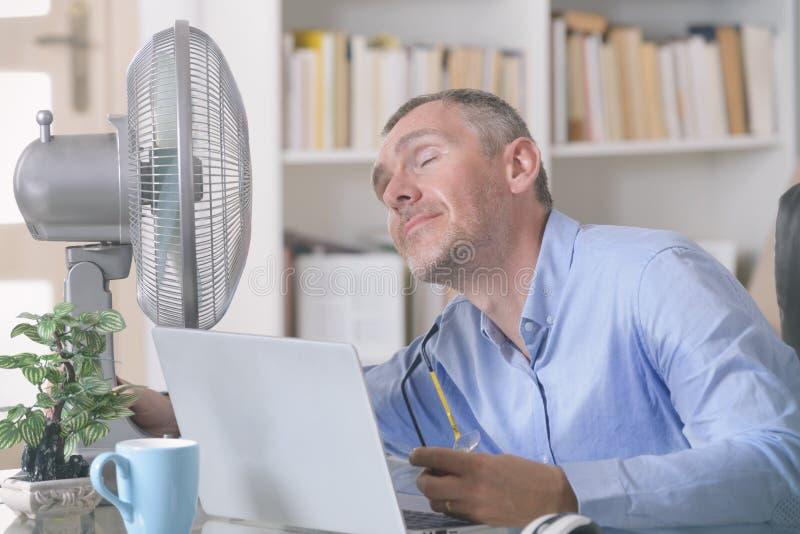 人遭受在家热在办公室或 库存图片