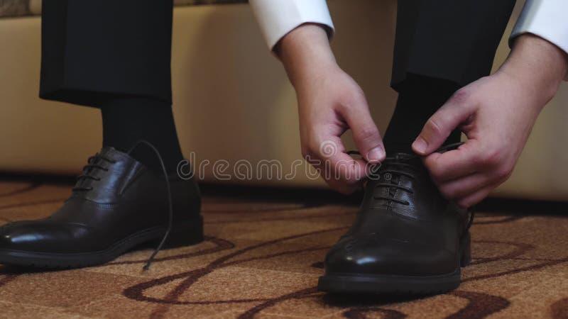 人阻塞他的在他的黑鞋子的鞋带 免版税库存照片