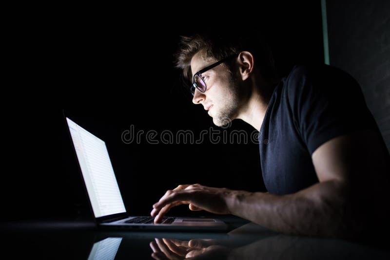 年轻人集中了在家使用便携式计算机的人户内在看膝上型计算机白色屏幕的晚上 免版税库存图片