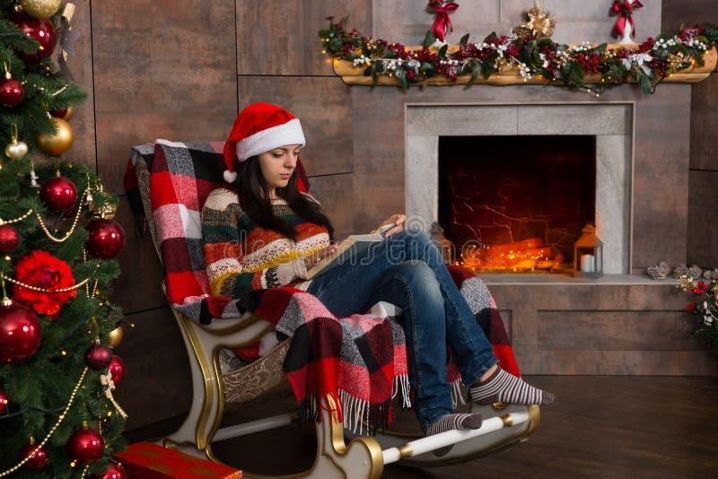 年轻人集中了滑稽的圣诞节帽子读书的妇女,当si时 库存照片