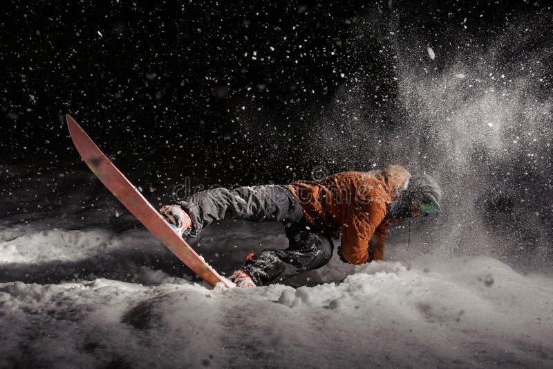 人雪板运动在雪下的晚上 免版税库存图片