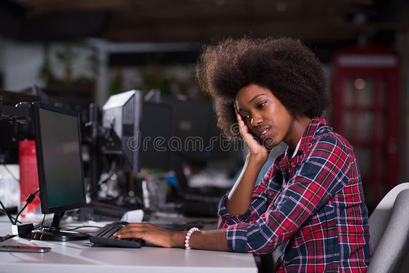 年轻人非裔美国人的妇女感到疲乏在现代办公室 免版税库存图片