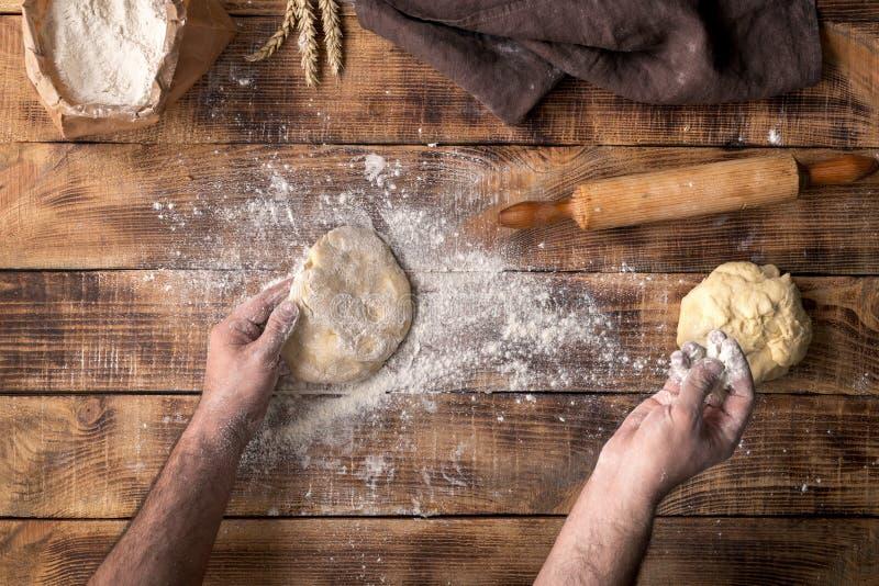 人面团为烹调在木桌上的薄饼做准备 免版税库存图片