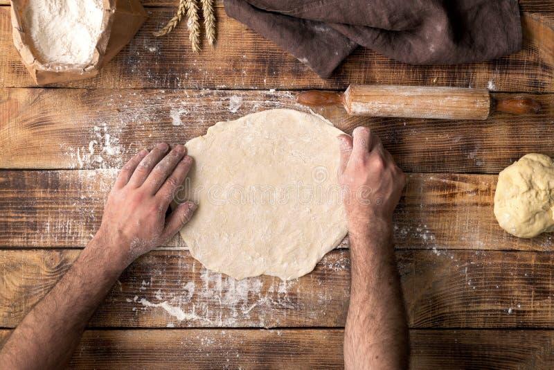 人面团为烹调在木桌上的薄饼做准备 库存图片
