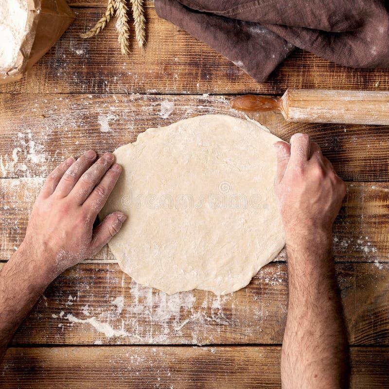 人面团为烹调在木桌上的薄饼做准备 库存照片
