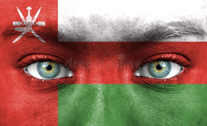 人面绘与阿曼的旗子 免版税库存照片