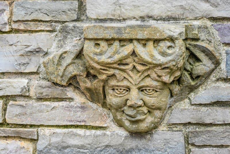 人面雕象在岩石墙壁的 图库摄影