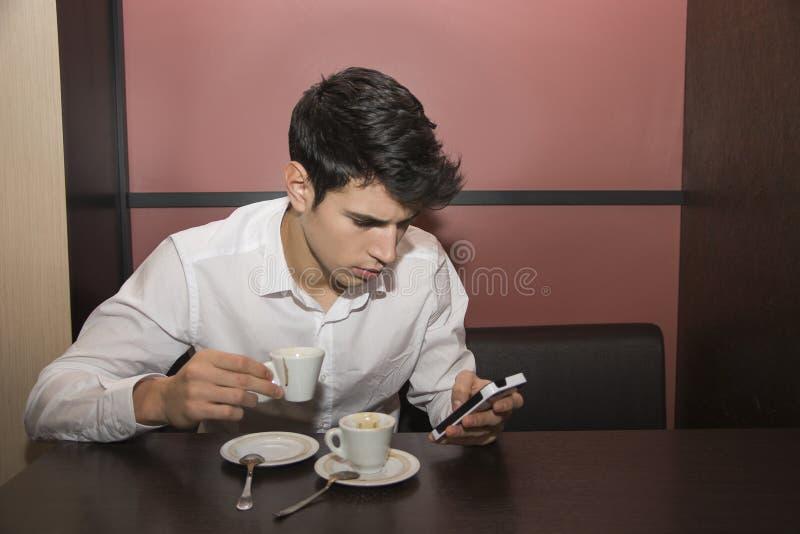 年轻人饮用的咖啡,当看手机时 免版税库存图片