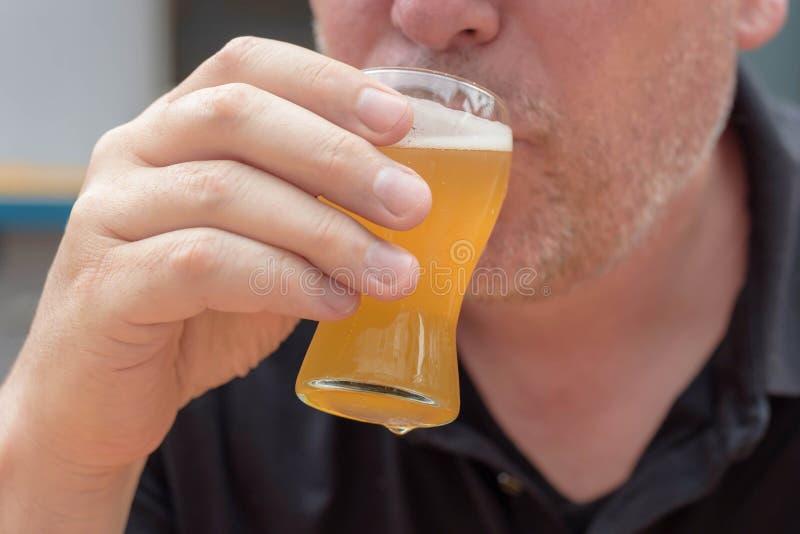 人饮用的啤酒特写镜头从品尝师玻璃的 免版税图库摄影