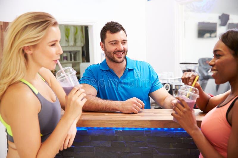 人饮用的蛋白质震动在健身房的健身酒吧 免版税库存图片