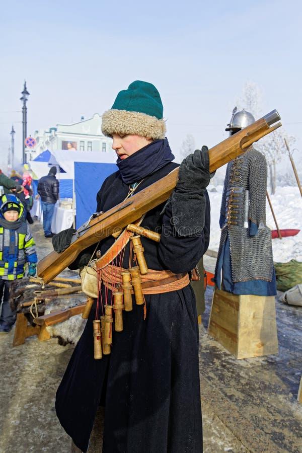人马座衣服的一个年轻人显示从18世纪步枪的步枪 库存图片