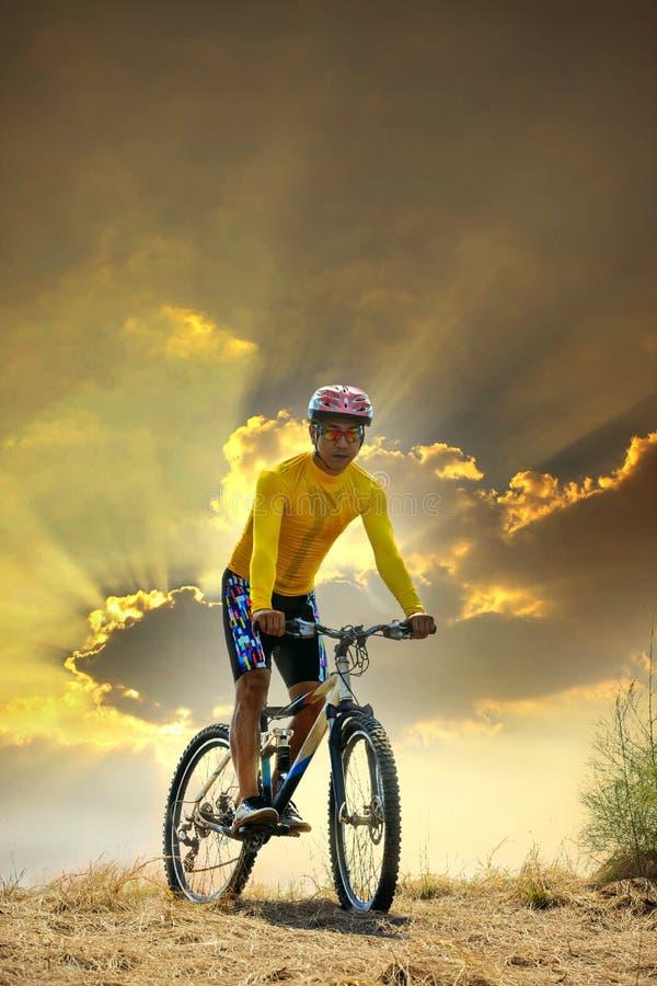 年轻人骑马moutain在土地沙丘的自行车mtb反对在晚上背景使用的暗淡的天空体育休闲和门activit的 图库摄影
