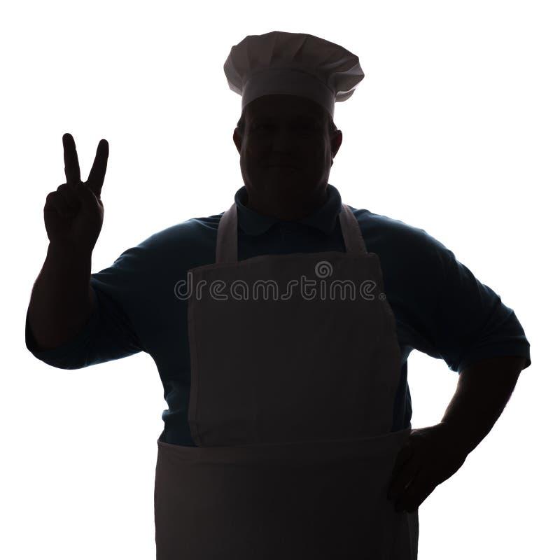 人,厨师剪影烹饪器材衣裳的显示与手指的一个招呼的姿态在白色被隔绝的背景,概念行业 免版税库存照片
