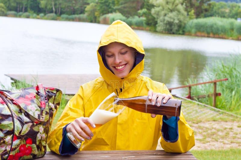 年轻人,喝麦子啤酒的妇女在一个雨天 免版税图库摄影