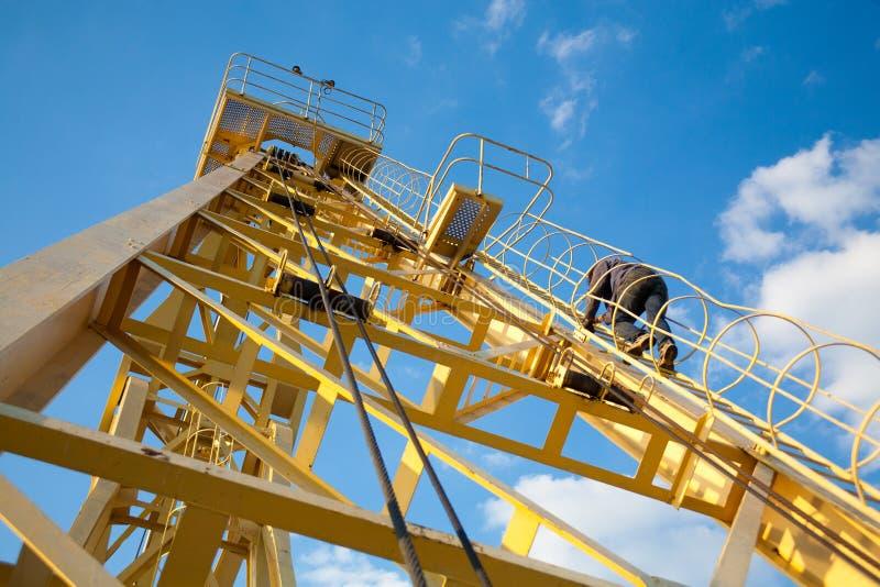 人,工作者,爬上台阶对黄色起重机industria 库存照片