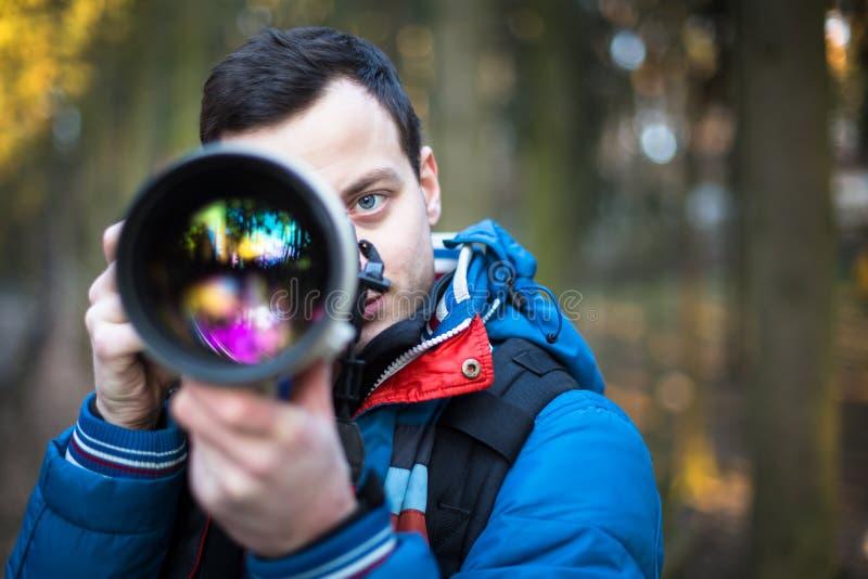 年轻人,拍与他的男性摄影师照片巨大 库存照片