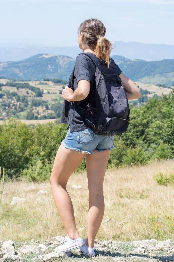 年轻人,有站立在高原的背包的女孩 免版税库存图片