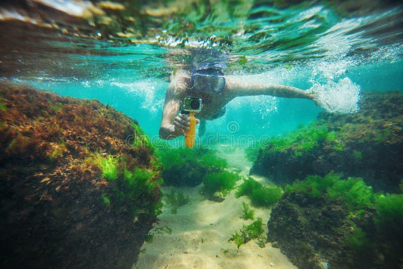 年轻人,游泳水下和做与体育照相机的照片 免版税库存照片
