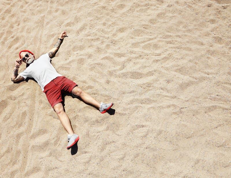 人,看起来圣诞老人,在沙子海滩说谎 免版税图库摄影