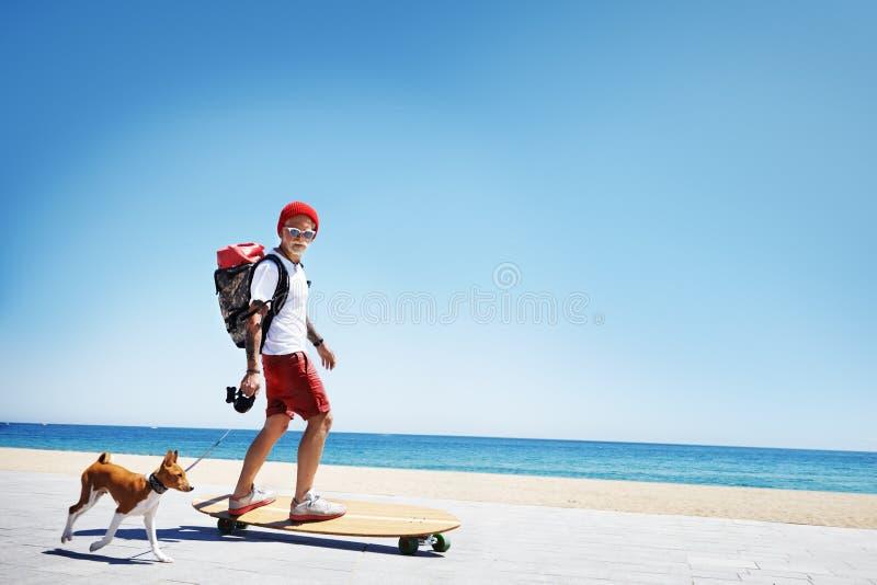 人,看起来圣诞老人,在海滩的乘驾longboard 免版税图库摄影