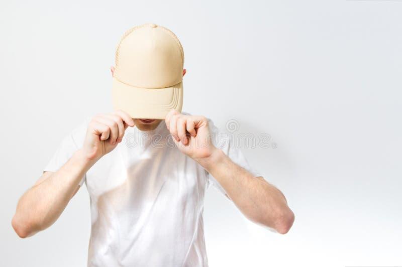 人,空白的白色,米黄棒球帽的人,在白色 免版税图库摄影