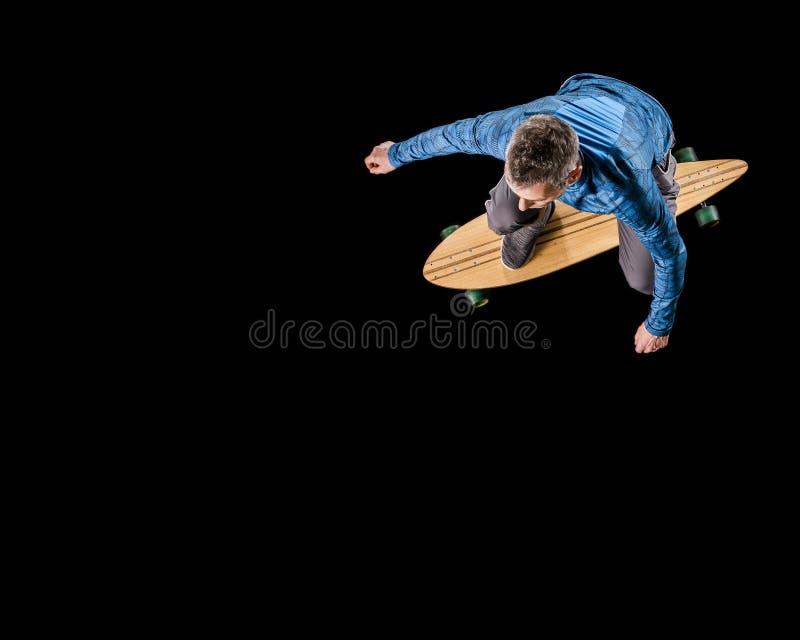人, 48岁,滑冰与longboard 免版税库存图片