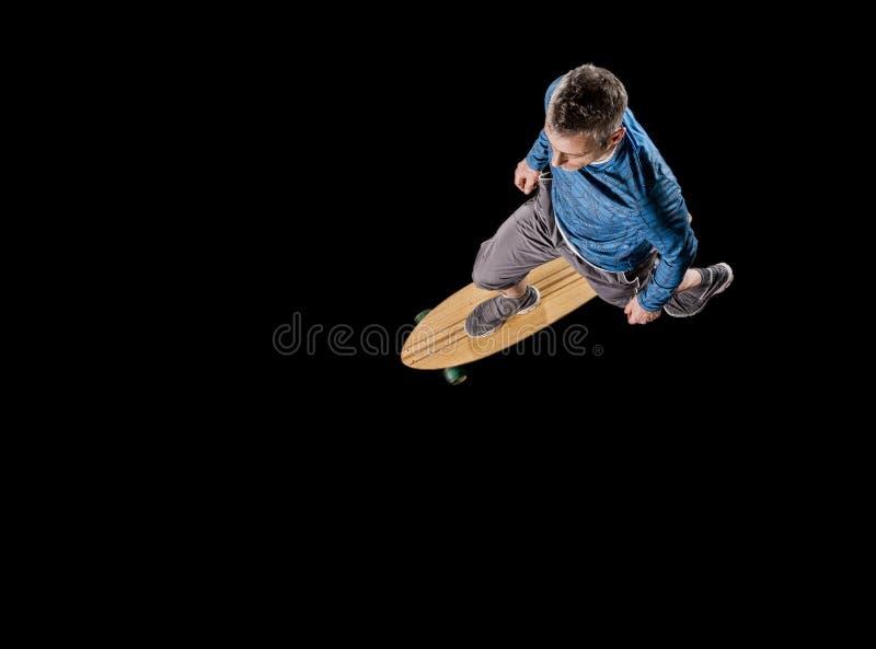 人, 48岁,滑冰与longboard 免版税库存照片