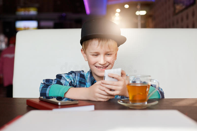 人们、休闲和现代技术概念 时髦的盖帽选址的快乐的小男孩在gener的咖啡馆饮用的茶读书sms 免版税库存图片