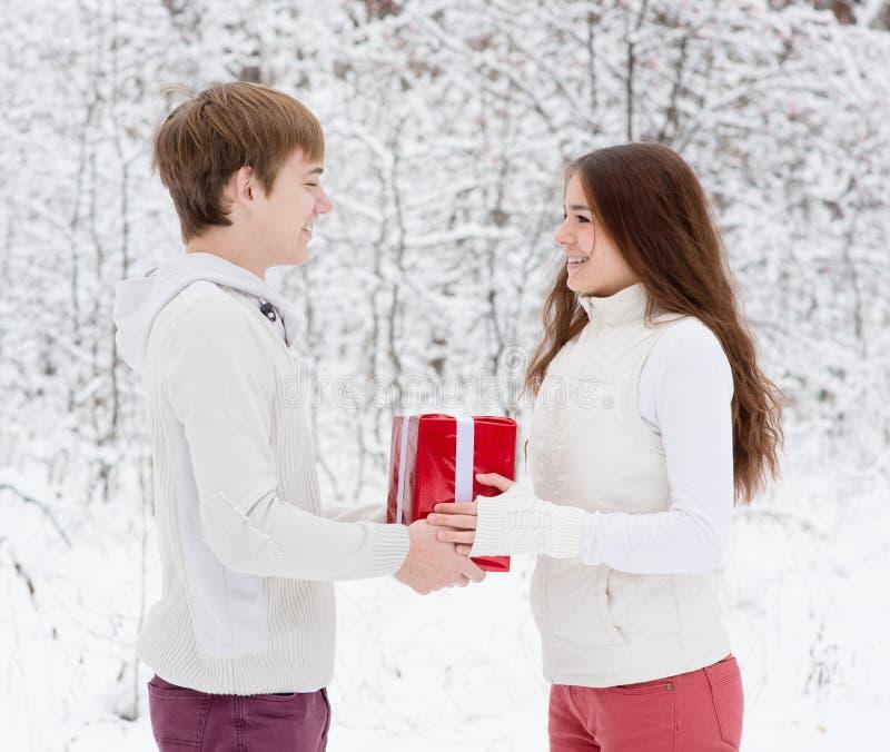 年轻人给一个礼物他的圣诞节的女朋友 库存照片