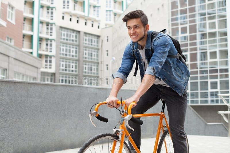人去一辆自行车的镇在蓝色牛仔裤夹克 年轻人橙色固定自行车 库存图片