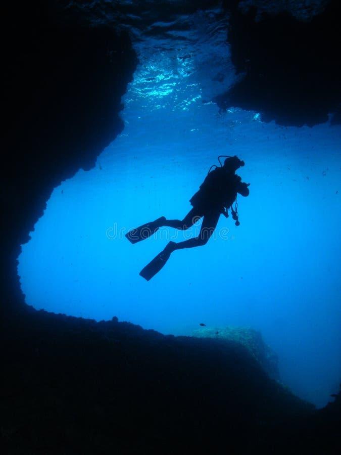 人水下的摄影师佩戴水肺的潜水洞 免版税库存图片