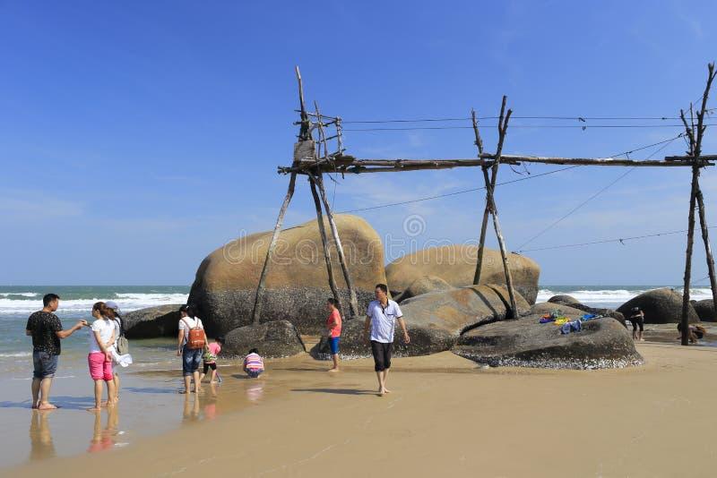 人们使用在岩石海滩木桥梁下  库存图片