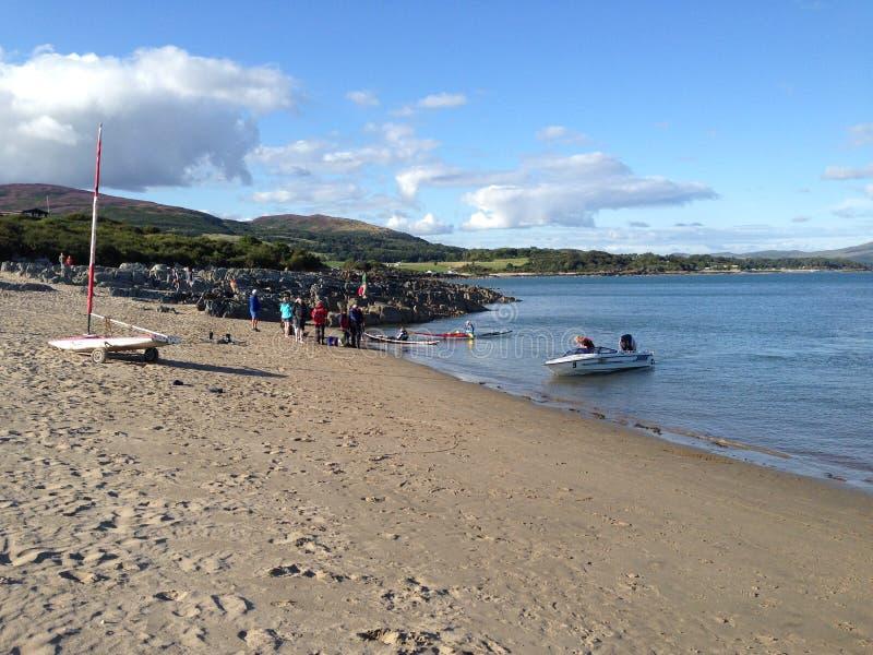 人们和小船在海滩 免版税图库摄影