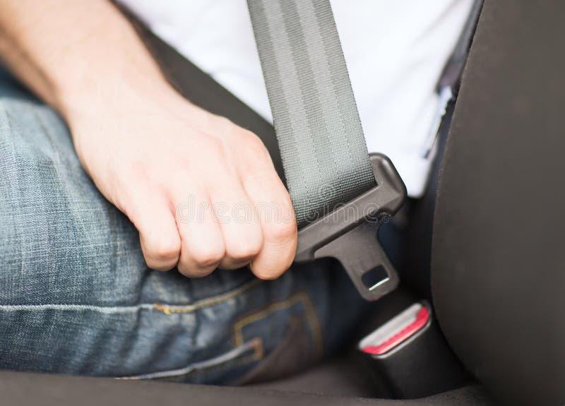 人紧固在汽车的安全带 库存图片