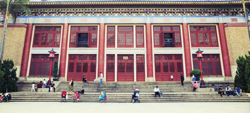 人们在与古典设计的中国传统建筑前享有休闲生活在古老东方样式 免版税图库摄影