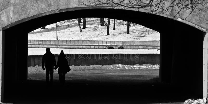 人们在曲拱的桥梁下 免版税库存照片
