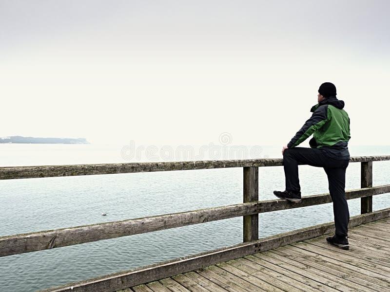 人以在海痣的绿色在扶手栏杆 秋天薄雾,雨天 库存照片