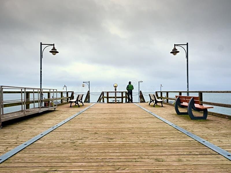 人以在海痣的绿色在扶手栏杆 秋天薄雾,雨天 免版税库存图片