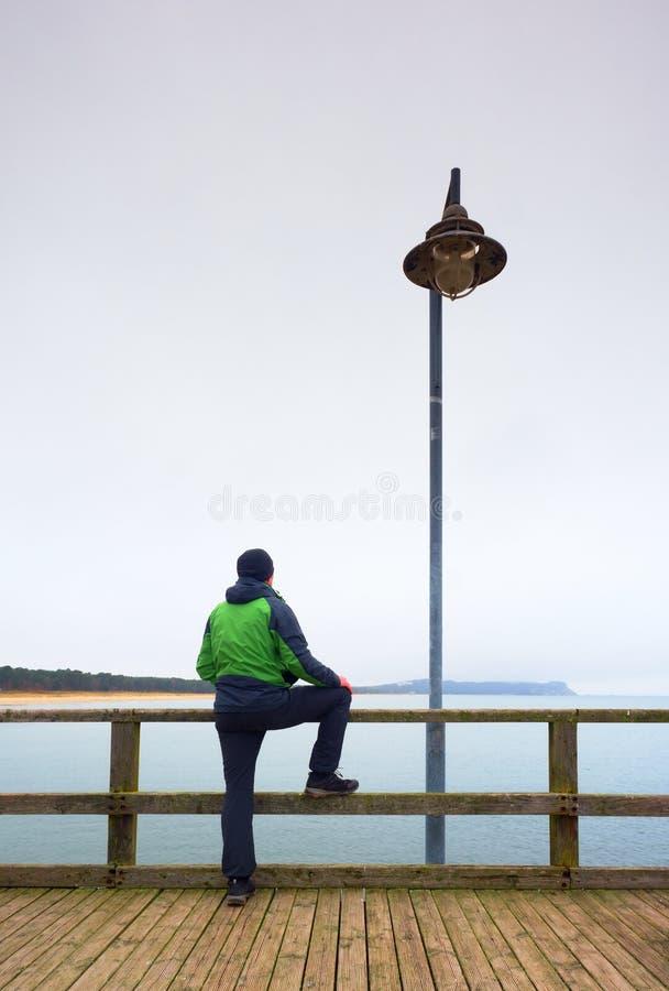 人以在海痣的绿色在扶手栏杆 秋天薄雾,雨天 免版税库存照片